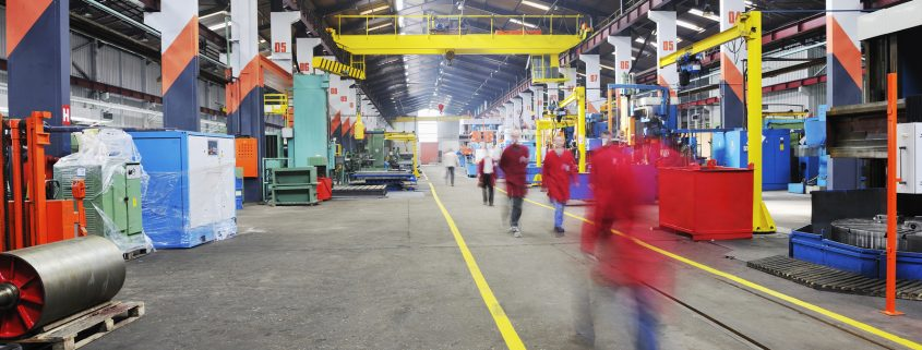 Colorful picture of a manufacturing facility with skilled technicians walking